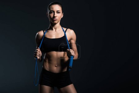 beautiful sportswoman with jump rope for cardio training, isolated on grey