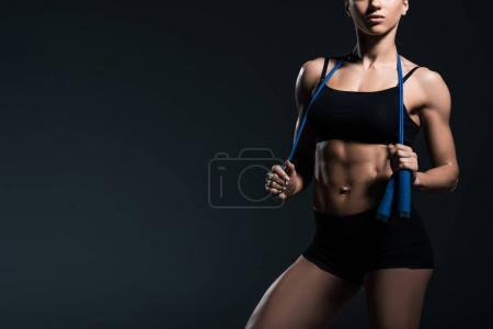 partial view of muscular sportswoman with jump rope for cardio training, isolated on grey
