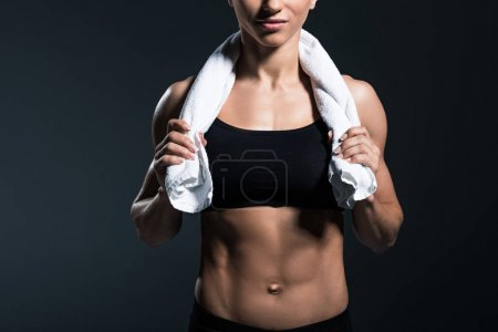 cropped view of muscular sportswoman with towel after training, isolated on grey