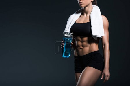 cropped view of muscular sportswoman with towel and water, isolated on grey