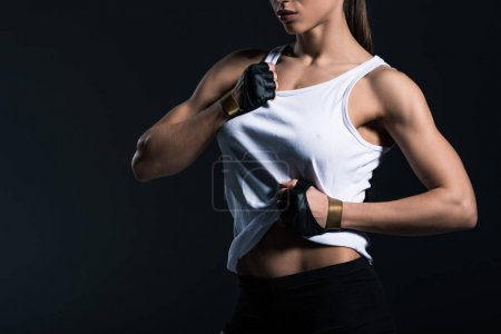 cropped view of muscular sportswoman showing abs, isolated on black
