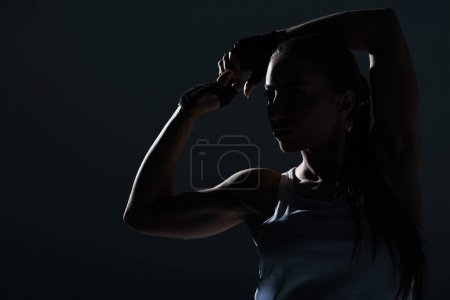 Photo for Silhouette of strong sportswoman showing muscular biceps, isolated on grey - Royalty Free Image