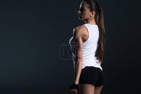 beautiful female bodybuilder posing in sportswear, isolated on grey