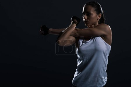 attractive muscular sportswoman stretching arm, isolated on black