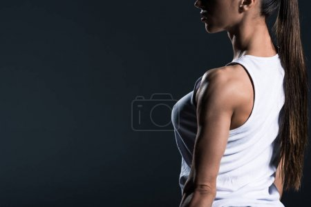 cropped view of muscular sportswoman posing in sportswear, isolated on grey