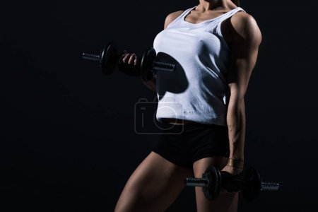 cropped view of sportswoman training with dumbbells, isolated on black