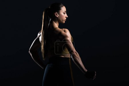 beautiful female bodybuilder posing and showing muscles, isolated on black