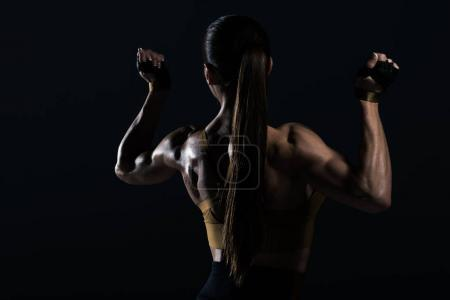 back view of strong female bodybuilder posing and showing muscles, isolated on black