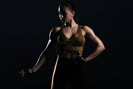 beautiful strong bodybuilder posing and showing muscles, isolated on black