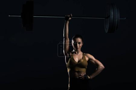 attractive strong bodybuilder holding barbell, isolated on black