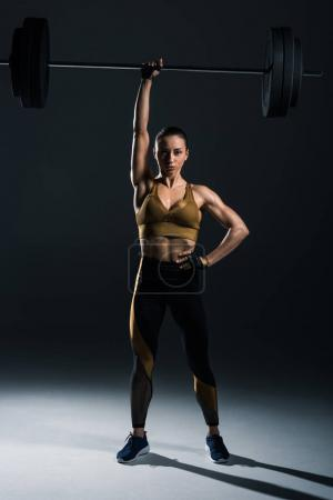 Photo for Young strong bodybuilder holding barbell, on black - Royalty Free Image