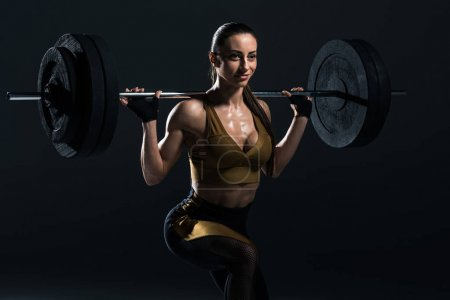 Photo for Beautiful young sexy bodybuilder squating with barbell, isolated on grey - Royalty Free Image