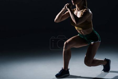 cropped view of sporty female bodybuilder doing lunges, on black