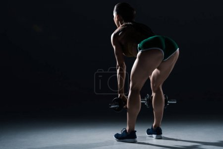 Photo for Back view of sexy female bodybuilder lifting dumbbells, on black - Royalty Free Image