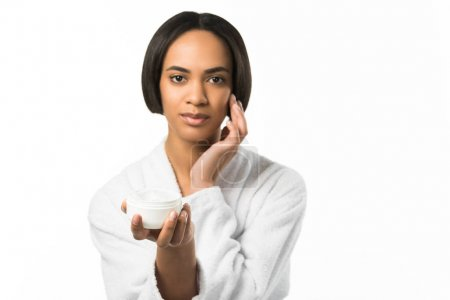 beautiful african american woman applying face cream,  isolated on white