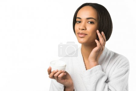 african american woman in bathrobe applying skin cream on face,  isolated on white
