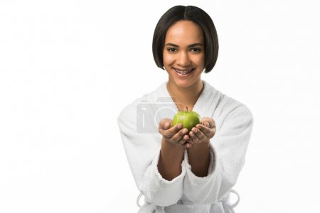 smiling african american girl with dental braces holding apple,  isolated on white