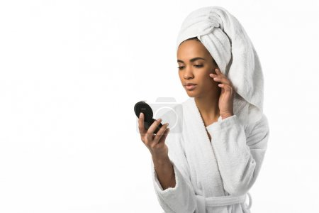african american woman in bathrobe and towel looking at mirror,  isolated on white