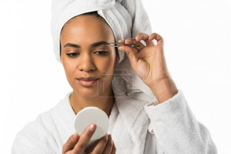 african american woman looking at mirror and plucking eyebrows with tweezers,  isolated on white