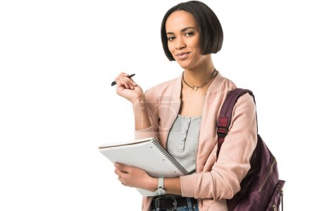 beautiful african american student with backpack writing in copybook,  isolated on white