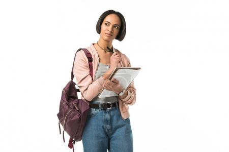 thoughtful female african american student with backpack writing in copybook,  isolated on white