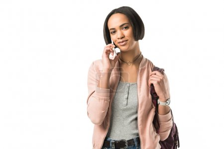 female african american student with backpack talking on smartphone,  isolated on white