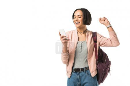 excited female african american student with backpack using smartphone,  isolated on white