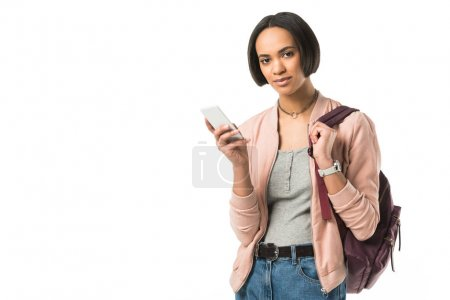 african american girl with backpack using smartphone,  isolated on white