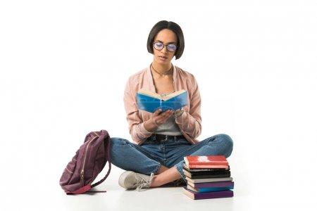 Photo pour Magnifique étudiant afro-américain lisant des livres assis sur le sol avec sac à dos, isolé sur blanc - image libre de droit
