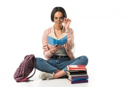 female african american student in glasses reading books while sitting on floor with backpack, isolated on white