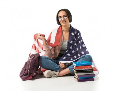 female african american student wrapped in usa flag sitting on floor with backpack and books, isolated on white