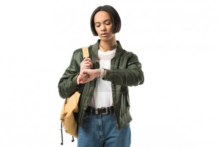 female african american student with backpack looking at wristwatch, isolated on white
