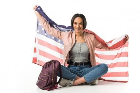 smiling african american student holding usa flag sitting on floor with backpack, isolated on white