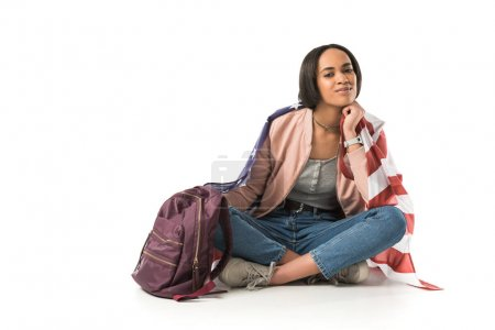 female african american student sitting on floor with backpack and american flag, isolated on white