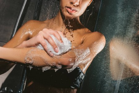 cropped view of african american woman washing body with foam and sponge in shower