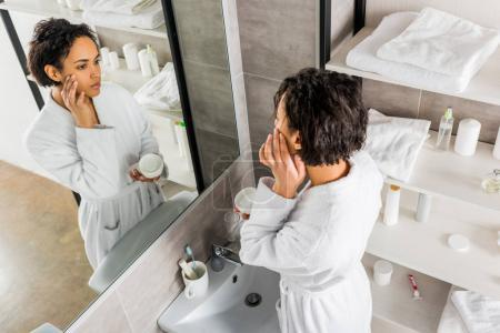 african american woman applying cosmetic anti-wrinkle cream on face and looking in mirror in bathroom