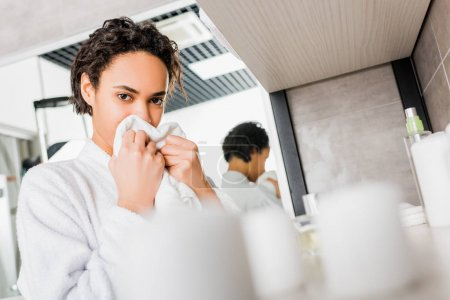 african american young woman sniffing fresh towel in bathroom