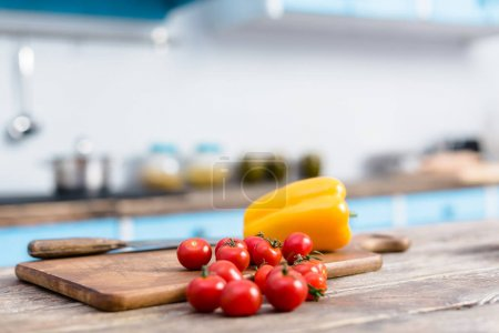 selective focus of fresh cherry tomatoes and bell pepper on tabletop with wooden cutting board and knife