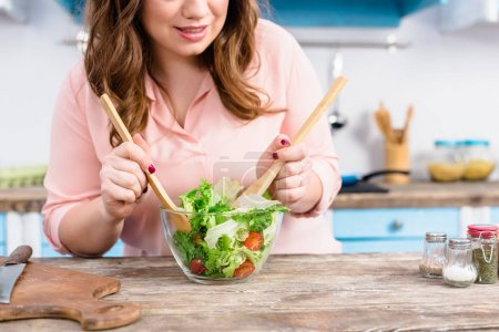 partial view of overweight woman cooking fresh salad for dinner in kitchen at home