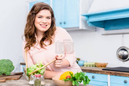 portrait of overweight smiling woman looking at camera while cooking fresh salad for dinner in kitchen at home
