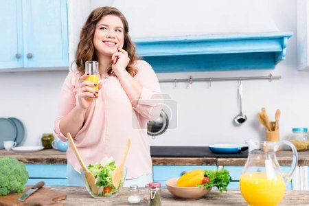 portrait of overweight smiling woman with glass of juice in kitchen at home
