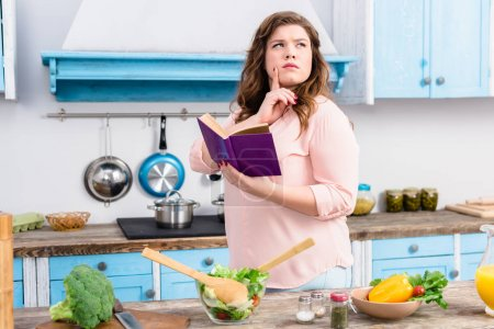 overweight pensive woman with cookery book standing in kitchen at home