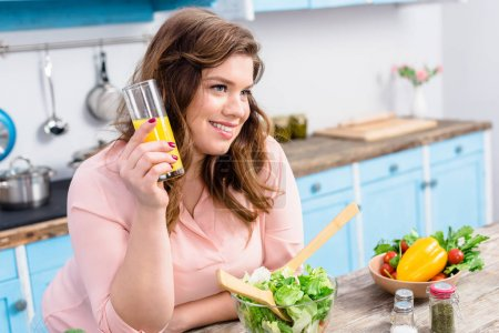 side view of overweight smiling woman with glass of juice in kitchen at home