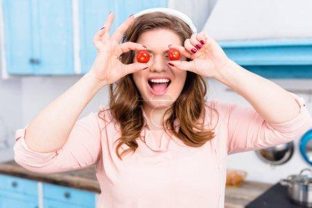 Photo pour Vue obscurcie de la femme en surpoids dans les écouteurs avec des tomates cerises dans les mains dans la cuisine - image libre de droit