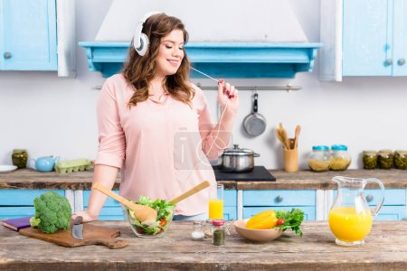 cheerful overweight woman listening music in headphones at table with fresh vegetables in kitchen at home