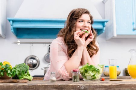 Photo for Overweight smiling woman at table with fresh salad in kitchen at home - Royalty Free Image