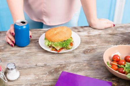 Photo for Cropped shot of overweight woman with soda drink standing at tabletop with burger - Royalty Free Image