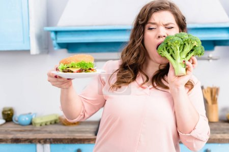 portrait of overweight woman with burger biting fresh broccoli in hands in kitchen at home, healthy eating concept