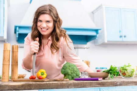 overweight smiling woman with knife at table with fresh vegetables in kitchen at home