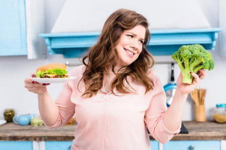 portrait of overweight woman with burger and fresh broccoli in hands in kitchen at home, healthy eating concept
